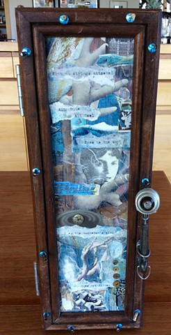 Vertical cabinet constructed with recycled barn wood, light bulb parts, old toy pot handle,collage, verbiage