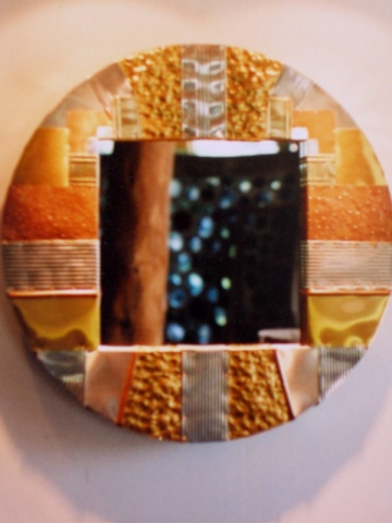 round mirror created from recycled metals with hammered textural areas copper, aluminum cans, etc