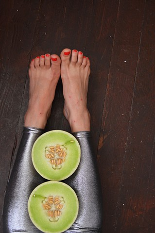photograph of woman feet legs honeydew melon food silver leggings fetish by Robyn LeRoy-Evans