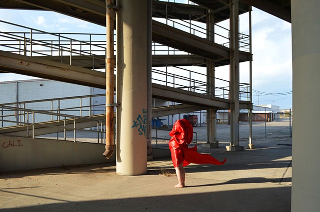 photograph of woman red drapery industrial landscape in New Orleans by Robyn LeRoy-Evans