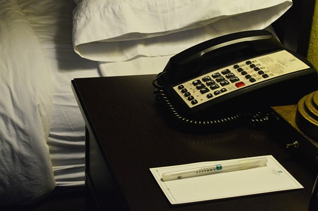 photograph of hotel room telephone notepad pen bed pillow sheets by Robyn LeRoy-Evans