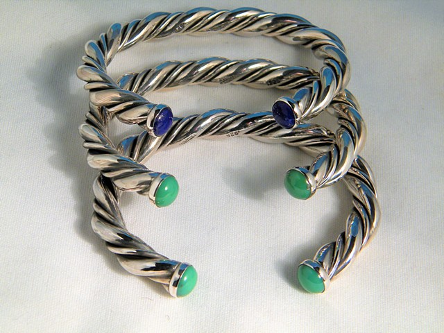 Three twisted silver cuffs.