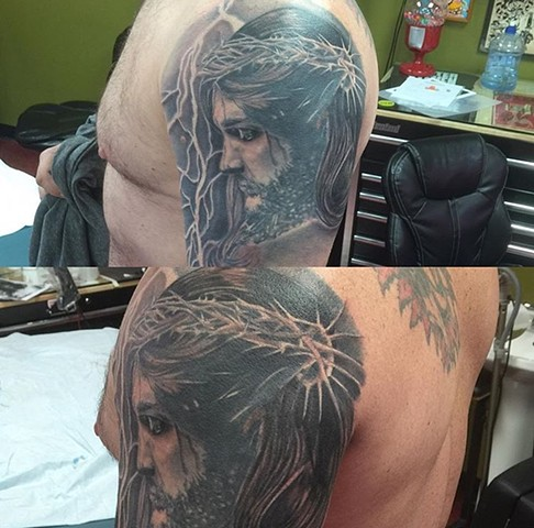 Jesus portrait tattoo in black and grey artwork on upper arm Strange World Tattoo Calgary, Canada