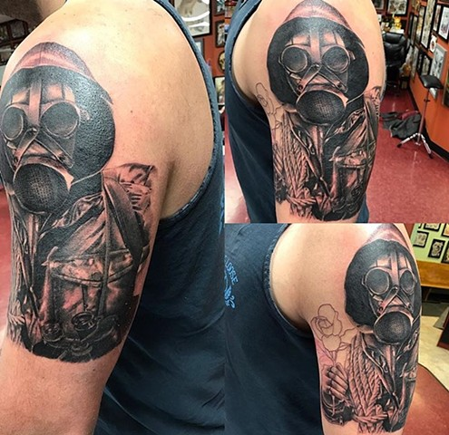 Soldier tattoo with gas mask in black and grey on upper arm Strange World Tattoo Calgary, Alberta Canada
