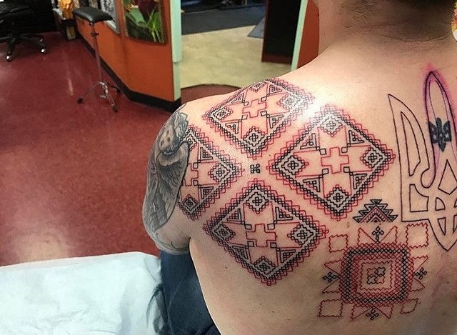 cross-stitch tattoo on shoulder blade Strange World Tattoo Calgary Alberta Canada