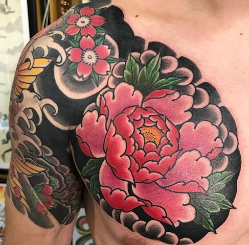 Flower tattoo in chest in colour strange World Tattoo Calgary Alberta Canada