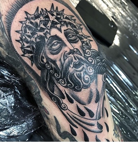 Jesus tattoo on a knee cap in black and grey Strange world tattoo Calgary Alberta Canada