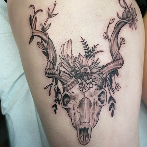 black and grey skull with antlers and flowers tattoo strange world tattoo calgary alberta