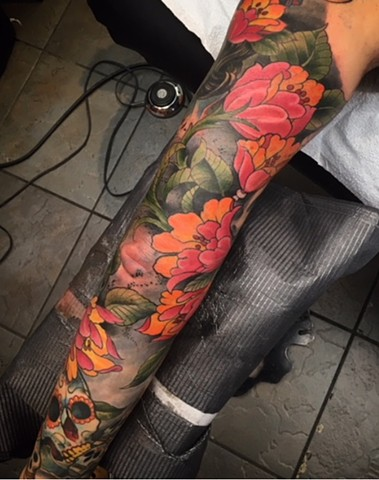 full colour sleeve of flowers and sugar skulls by tattoo artist Brett Schwindt in Calgary, Canada