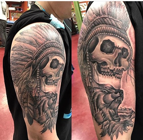 Skull with headdress half sleeve tattoo in black and grey Strange World Tattoo Calgary Alberta Canada
