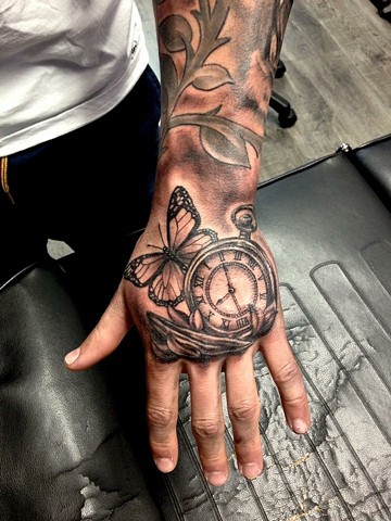 butterfly and pocket watch tattoo on a hand strange world tattoo