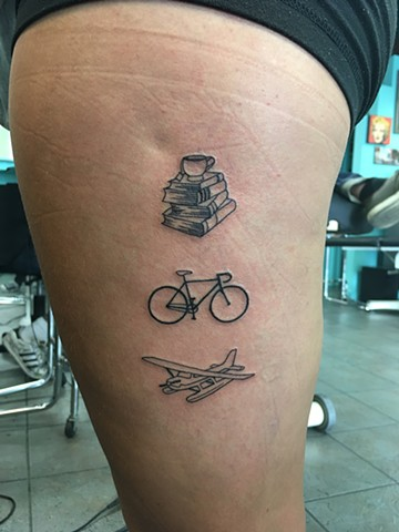 books, bike and plane tattoo