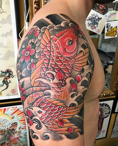 koi fish tattoo on upper arm in colour Strange World Tattoo Calgary Alberta Canada