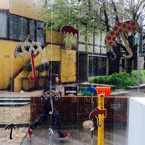 . Rainy day in Vancouver. Ceramic umbrellas hanging in          a studio window