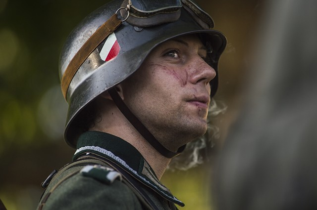 A re-enactor portraying a World War II German soldier enjoys a cigarette while awaiting a recreated battle against Allied forces.