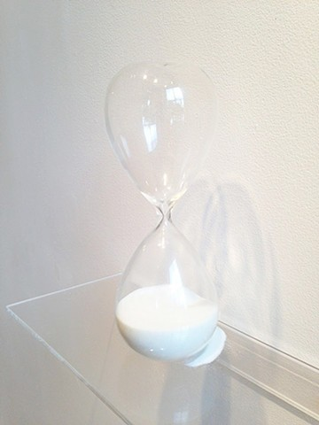 An hourglass with a crack in the back, leaks sand, and time. Sculpture by artist, writer, curator, Darren Jones