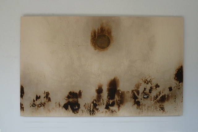 Golden circle of honey and pigment in center of large canvas, smoke markings allong bottom, some scorches.