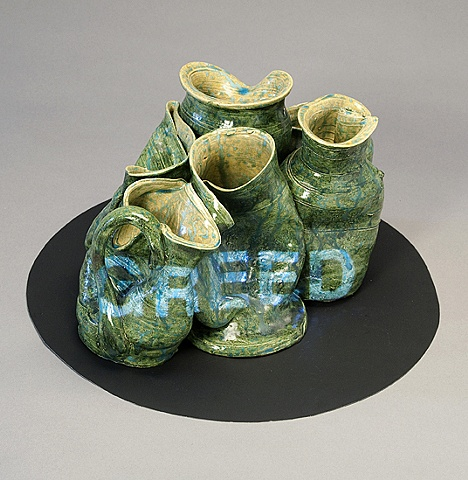 "Wheel thrown and altered ceramic vessels with projected text ""Greed"" by Linda S Fitz Gibbon"