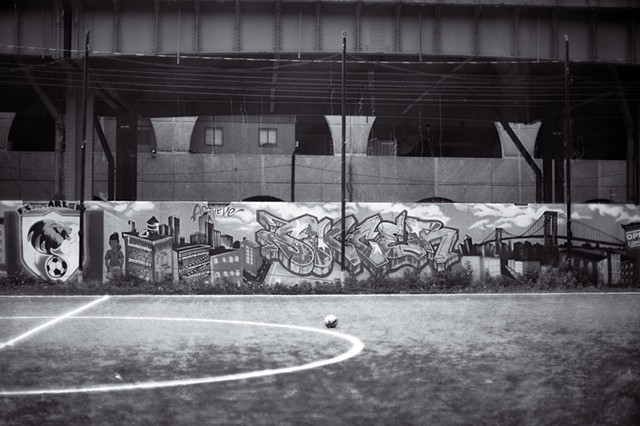 Photograph of a soccer ball in front of a graffiti covered wall along the Hudson River Greenway, Manhattan, New York, by Judith Ebenstein