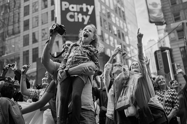 Photograph of a girl on her father's shoulders, Times Square, Manhattan, NY, by Judith Ebenstein