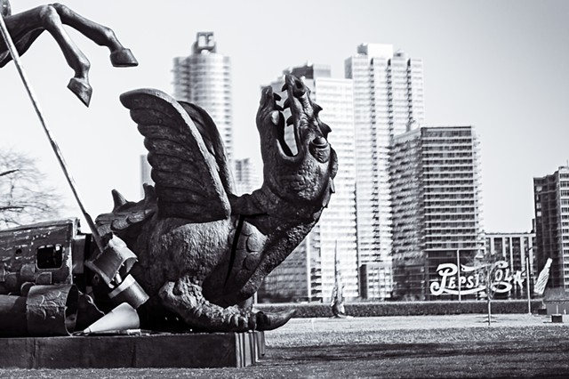 Photograph of a dragon being slain by St George on the grounds of the United Nations building with the Pepsi Cola sign and Queens in the background, by Judith Ebenstein