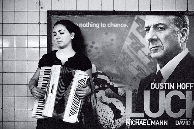 Photograph off an Accordionist with a Poster of Dustin Hoffman, 14th St Subway Station, Manhattan, New York, by Judith Ebenstein