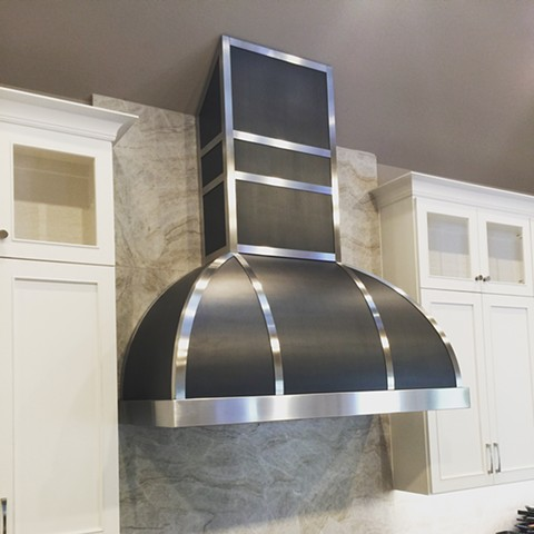 Blackened steel and stainless steel convex range hood.