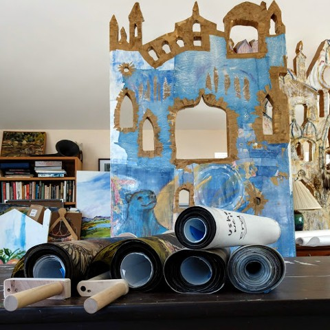 "A stack of crankie scrolls in front of ""The Big Blue Bear Theater""  painting"