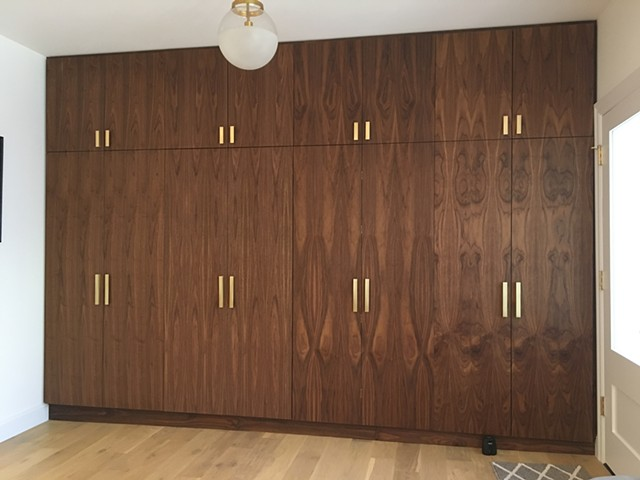 Altered existing walnut cabinetry to house a TV and components. The four middle doors were made into bifold doors, added wide swing hinges, cut out some of middle verticale panels, and added a cabinet insert with four doors to house accessories.