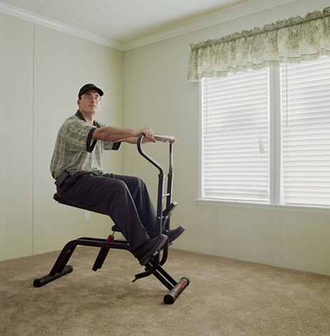 Man on excercise bike in manufactured display home, © Amy Eckert www.amyeckertphoto.com