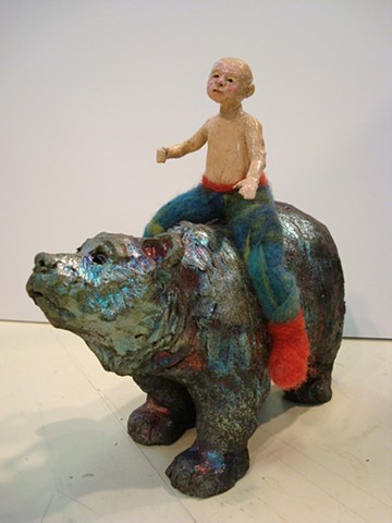 small boy rides a raku bear
