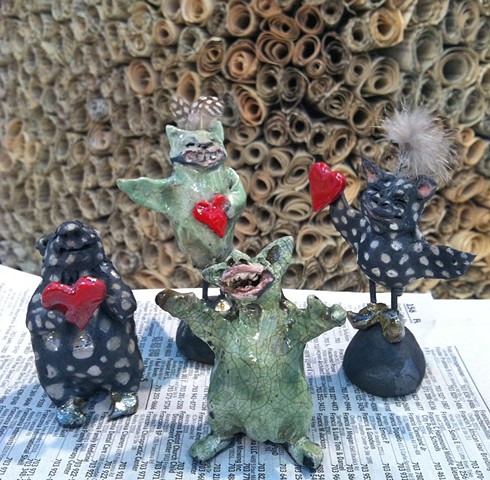 four little monsters made of raku ceramics and feathers by lisa schumaier