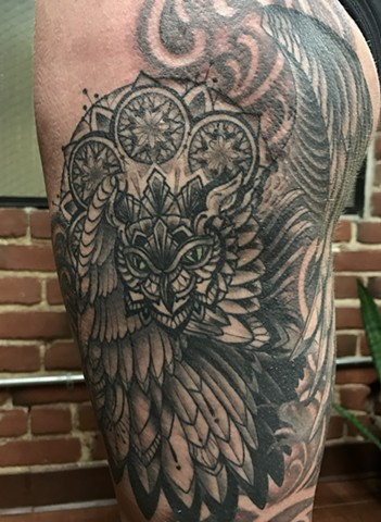 this is a tattoo done in a gothic dark art style by amanda marie tattooer of an owl spirit animal with a mandala halo and a pocket watch done in black and grey with soft shading amanda works at ace of wands tattoo in san pedro los angeles california