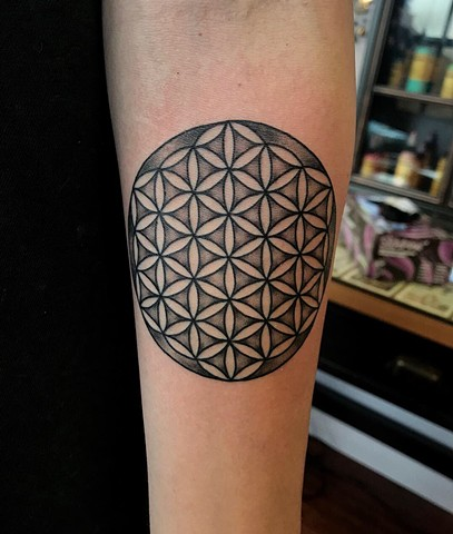 this is a tattoo of the flower of life done in black and grey by Amanda Marie female tattoo artist and owner of ace of wands private tattoo studio and sacred space