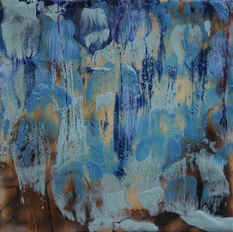Waterfall in shades of blue over rocks outlined with sepia created with a wood burning tool.