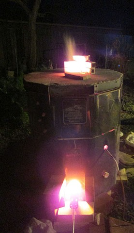 The propane gas kiln firing at night.