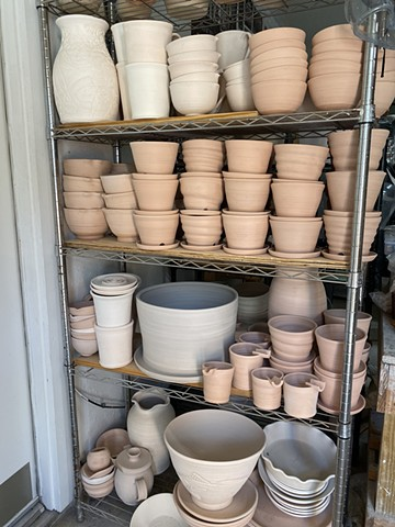 Pots in studio ready for glaze or bisque firing