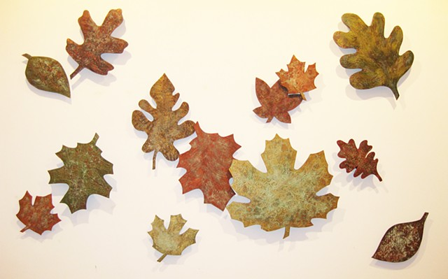 Elevated wall art sculptures made of wood shaped leaves with metallic texture.