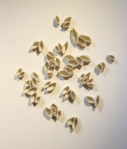 Contemporary seeds made of wool dipped in beeswax that create deep shadows.