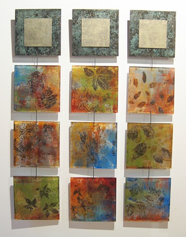 Individual wall art paintings inspired by nature hung from hooks to create installation sculpture abstract art