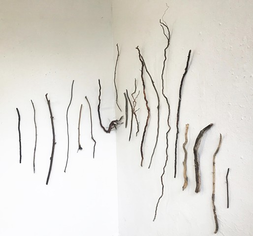Found driftwood wall sculpture in a line shape drawing contrast