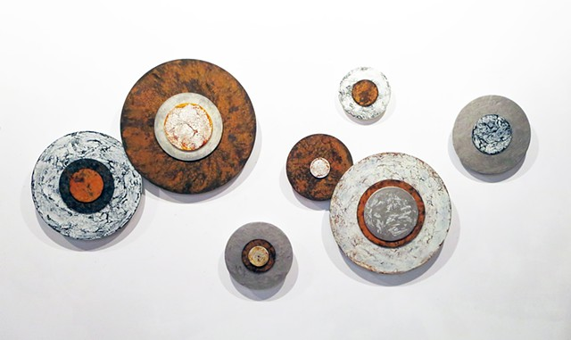 Cotemporary, modern wall sculpture art with rust on dimensional circles on acrylic panels