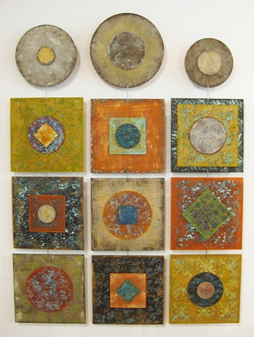 Hanging wall art sculptures with circular and square panels, orange and metallic finishes