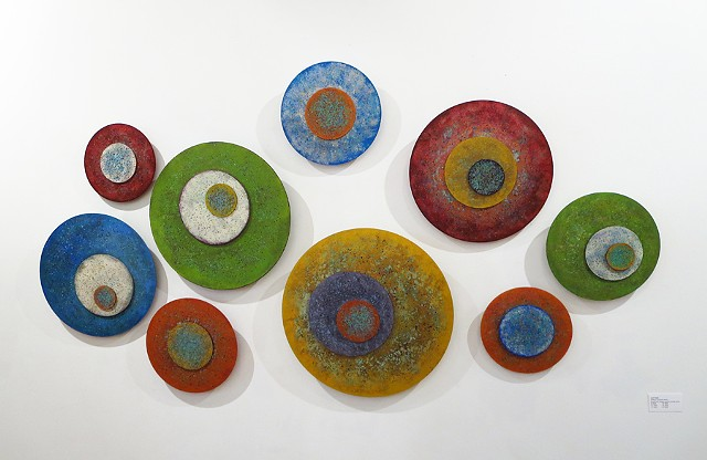 Wall sculpture installation of several circular paintings on acrylic panels.