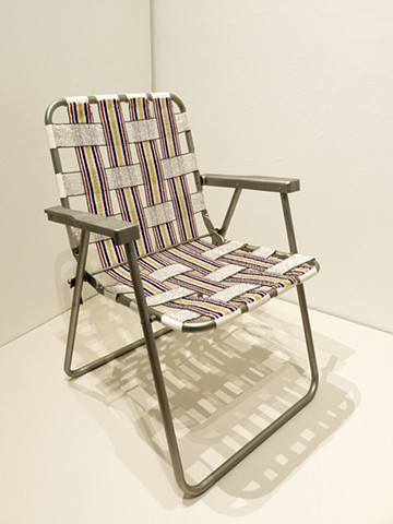 A lawn chair covered in loom-beaded sections of glass beads copying an original chair.