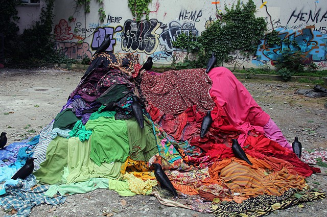 Art installation by artist Paul March, entitled Welcome to the Pleasure Dome, resembling crows on multicoloured pile of clothes in wasteland