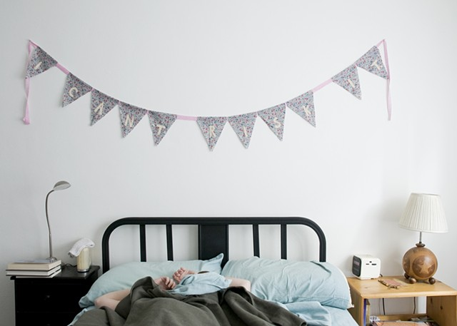 "Bunting banner reading, ""I can't risk it"" hanging above figure in unmade bed."