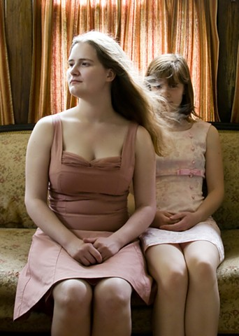 Self portrait of sisters in pink dresses, one with long hair blowing in front of the other's face.