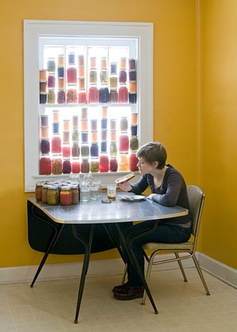 Self portrait in yellow room eating toast. Window is filled with canning jars full of jam, preserves.