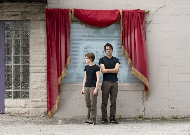 Self portrait with boyfriend in front of red curtain. Wearing matching outfits, black shirt and brown pants.
